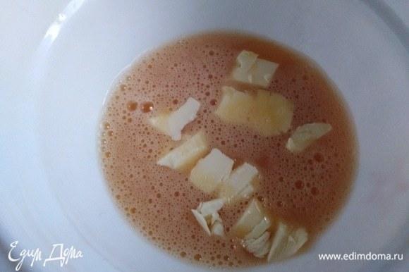 За это время яйца поменяют цвет. Добавить к ним нарезанное кусочками сливочное масло. Влить молоко. Перемешать.