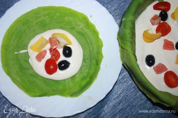 На отдельную тарелку выкладываем блин, сверху — крем и заполняем блинчик всеми ингредиентами начинки (рыбой, помидорами, маслинами и сладким перцем).