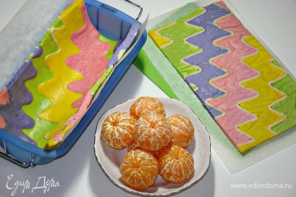 Форму выстлать пекарской бумагой и уложить бисквит. Мандарины очистить от кожуры.