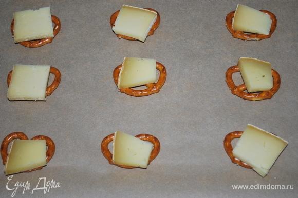 На брецели положите по кусочку сыра и поставьте запекаться в разогретую до 170°C духовку на 3–4 минуты, пока сыр не расплавится. Возьмите столько кренделей, сколько хотите приготовить закуски.