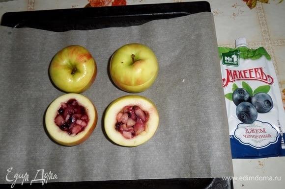Противень застилаем пергаментом. Выкладываем на пергамент яблоки. Внутрь каждого выкладываем приготовленную яблочно-черничную начинку. Накрываем срезанными верхушками.