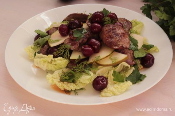Листья салата вымыть, обсушить, порвать на мелкие кусочки. Мелко нарезать укроп и петрушку. На тарелку выложить листья салата, на них — теплую (не горячую!) печень. Сверху — ломтики груши и еще слой печени. Полить маслом, в котором жарилась печень, сбрызнуть соком лимона. Посыпать салат зеленью. Сверху выложить вишню. Подавать салат теплым.