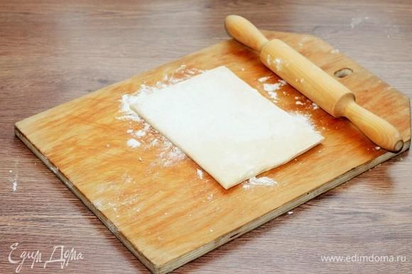 Размороженное слоеное тесто выложить на подпыленную мукой разделочную доску и раскатать до увеличения в длине в 2 раза.
