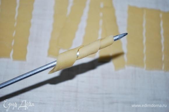 Возьмите толстую вязальную спицу и оберните вокруг нее полоску теста (спицу окунайте в муку, чтобы тесто не липло). У вас получится спираль.