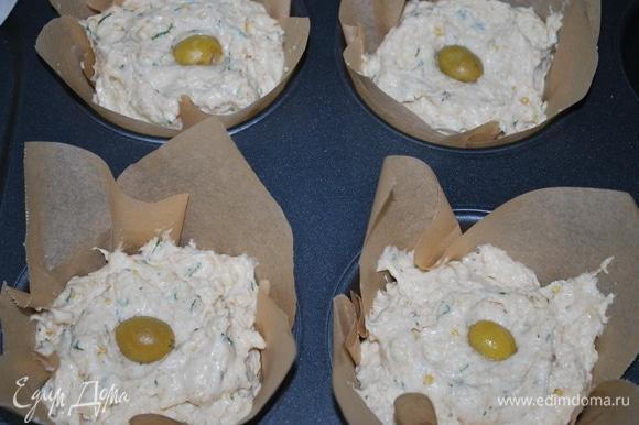 Выложите тесто в подготовленную форму (я выпекала эти маффины в больших формах). В центр выложите оливку и посыпьте семечками. Выпекайте в разогретой духовке при 170°C 45–50 минут до готовности.