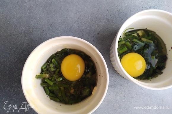 В каждую кокотницу разбить по 1 или 2 яйца.