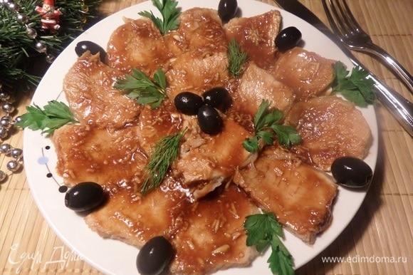 По прошествии определенного времени вынимаем мясо из холодильника, украшаем зеленью и маслинами. Подаем на стол.