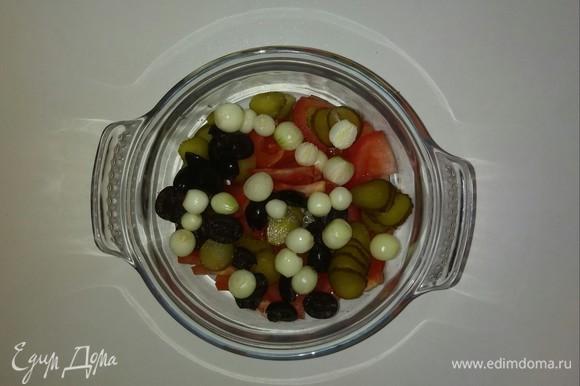 В глубокую емкость кладем нарезанные помидоры, маслины, малосольные огурцы и головки лука-севка. Если вы используете обычный репчатый лук, то нарежьте его кубиками. Перемешиваем.