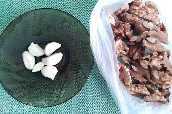 Приготовить орехи и очищенный чеснок.