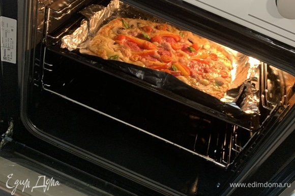 Отправляем пиццу в духовку. Выпекала первые 10 минут при 200°C, далее уменьшила до 180°C и следила за тем, когда все подрумянится. Ушло еще минут 5. Но лучше смотрите по краям пиццы. Она может быть готова быстрее. Зависит от толщины теста.