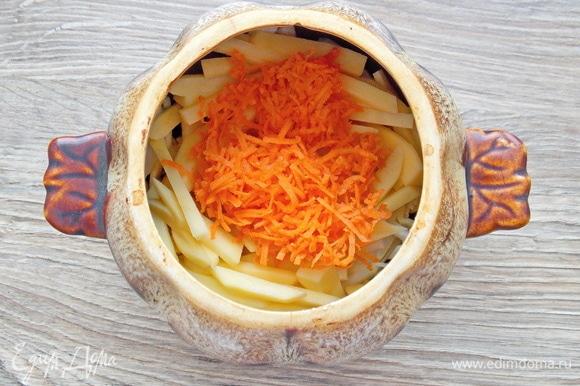 Морковь очистим, сполоснем и натрем на мелкой терке. Добавим в горшок с овощами.