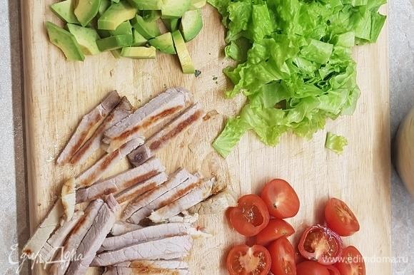 Листья салата нарезать, черри — на половинки, буженину — брусочками. Авокадо очистить от кожицы, удалить косточку. Каждую половинку разрезать на четвертинки и на ломтики.