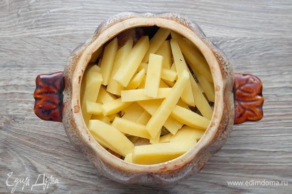 Картофель чистим, моем и режем соломкой или кубиком — как удобно. Кладем картофель в горшок к грибам.