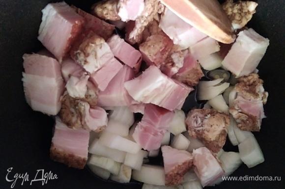 В казане разогреть растительное масло, добавить лук и нарезанную грудинку. Жарить 5 минут.