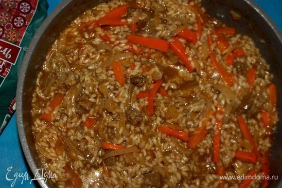 Готовим, пока рис не впитает всю воду. Не забываем помешивать. Рис должен получиться мягким, но внутри быть чуть твердым. По консистенции будет напоминать ризотто. Пока блюдо доходит на огне, подготовим лук. Такой лук называется отбитым. Половину луковицы, которую откладывали, режем полукольцами. Нарезанный лук мнем руками, пока он не станет мягким. Промываем холодной водой, чтобы ушла лишняя горечь, но острота осталась.