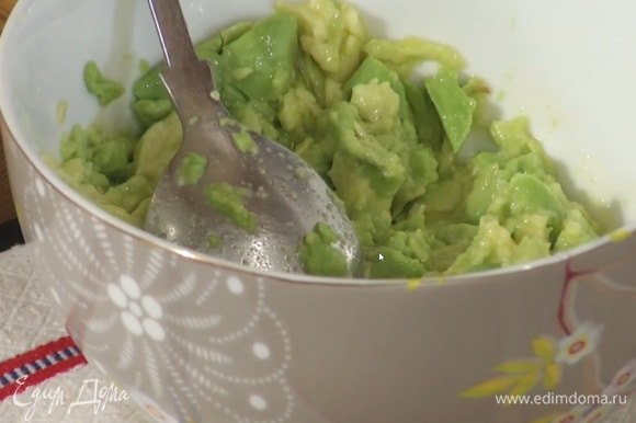 Авокадо разрезать пополам и удалить косточку, ложкой вынуть мякоть и выложить в глубокую пиалу, влить оливковое масло, сок лимона, посолить и размять.