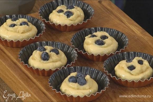 Охлажденное тесто разложить в формочки так, чтобы получились бортики, и смазать яйцом, в центр выложить по 1 ч. ложке крема и украсить ягодами голубики.