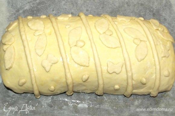 Переворачиваем кулебяку швом вниз. Кладем на противень, застеленный смазанной растительным маслом пекарской бумагой. Одно куриное яйцо взбить, немного смазать кулебяку, чтобы украшения хорошо держались. Украшаем остатками теста.
