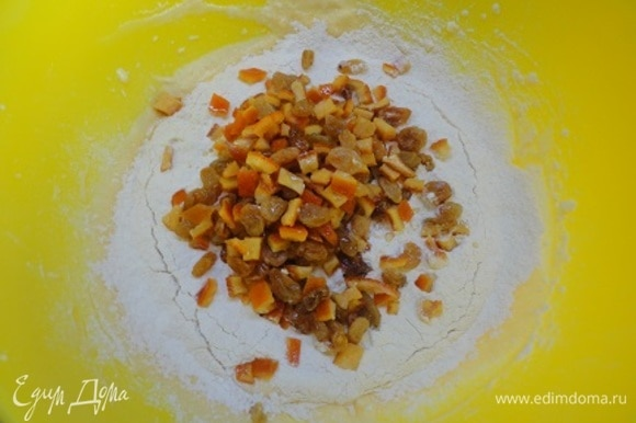 К яично-масляной массе добавить цедру апельсина, аккуратно просеять сухую смесь, а также цукаты и изюм.