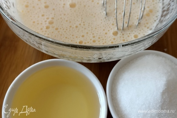 Продолжая взбивать, добавить сахар и подсолнечное масло.