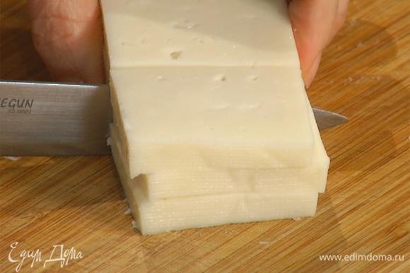 Сыр нарезать крупными ломтиками толщиной 1/2 см, затем разрезать их пополам.