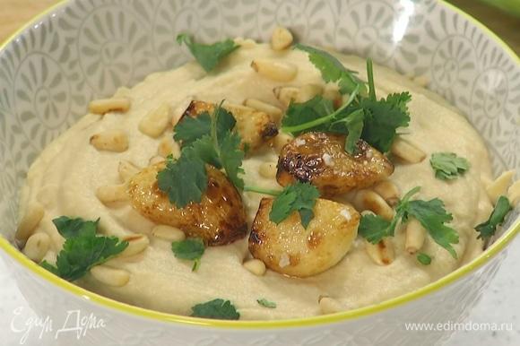 Готовый хумус переложить в салатницу, украсить кедровыми орехами, обжаренным чесноком и листьями кинзы.