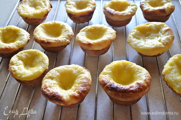 Готовые пирожные достаньте из формы и остудите на решетке, посыпьте сахарной пудрой и корицей.