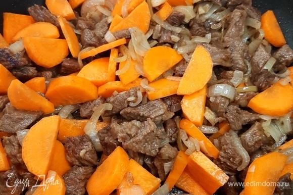 Морковь нарезаем полукольцами средней толщины и отправляем ее к мясу, поджариваем пару минут.