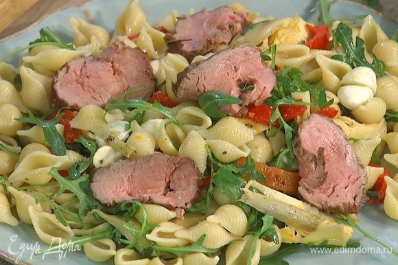 Выложить салат на большую тарелку, сверху разложить кусочки ростбифа.