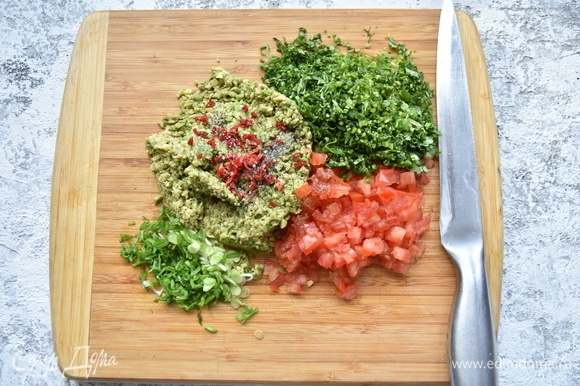 Мелко нарезать помидор, предварительно удалив из него жидкую часть с семенами. Измельчить зеленый лук, кинзу, красный острый перец.