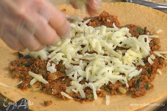 На две тортильи тонким слоем равномерно выложить начинку, посыпать натертым сыром, затем накрыть лепешкой без начинки и прижать.