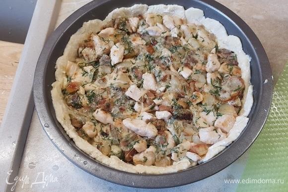 Достать тесто из холодильника и разделить на две неравные части. Большую часть раскатать в круг и выложить в форму для выпекания, сформировать бортики. Выложить начинку и немного ее утрамбовать.