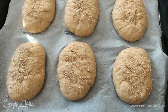 Переложить булочки на противень. Сверху сделать надрезы, посыпать кунжутом и солью.