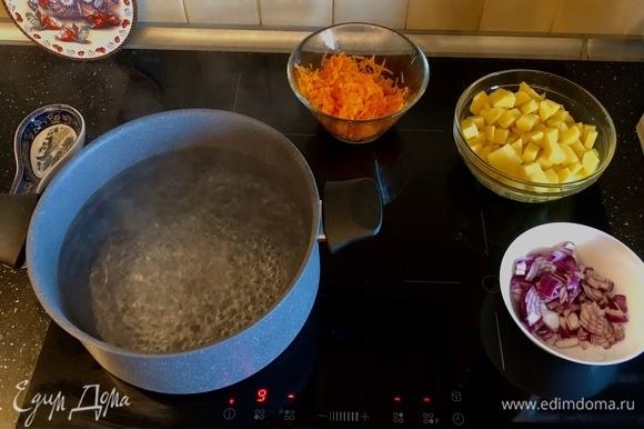 Добавить картофель, морковь и лук в кипящую воду.