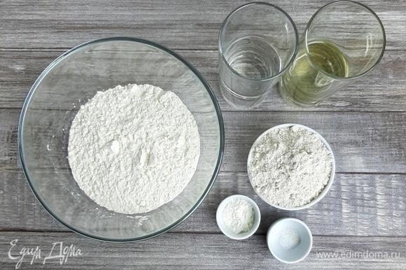 Смешиваем муку, соль и разрыхлитель. Добавляем растительное масло без запаха и теплую воду. Замешиваем тесто.