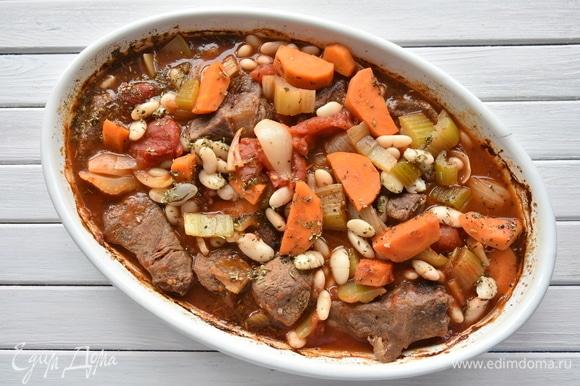 Достать рагу из духовки, добавить подготовленную фасоль и обжаренные свиные колбаски, аккуратно перемешать. По необходимости влить воды. Снова накрыть форму фольгой и запекать еще 1–1,5 часа.