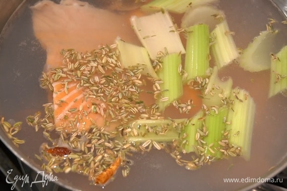В большую тяжелую кастрюлю влить холодную воду, выложить панцири креветок, голову и ребра семги, морковь, сельдерей и раздавленный чеснок, добавить семена фенхеля и пеперончино и довести до кипения, затем снять пену, посолить и варить 30‒40 минут.