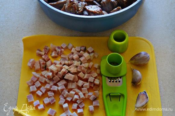 Тем временем бекон нарежьте мелкими кубиками. Чеснок почистите и измельчите с помощью чеснокодавилки. Поместите бекон в сотейник, в котором обжаривалось мясо, и слегка поджарьте. Добавьте туда же измельченный чеснок и готовьте 2 мин, перемешивая.