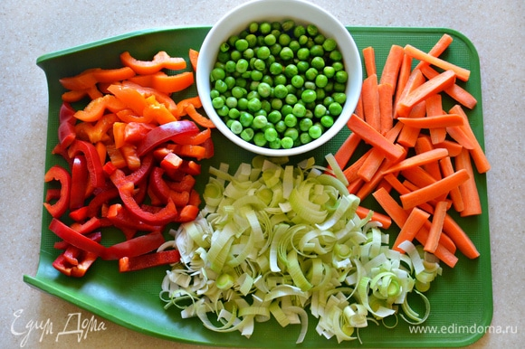 Зеленый горошек предварительно разморозьте. Морковь необходимо почистить и нарезать брусочками (небольшую морковь разрежьте вдоль на 4 части и затем нарежьте на куски по 3 см). Болгарский перец очистите от семян и плодоножки, нарежьте на небольшие полоски. Лук-порей (нам понадобится белая или светло-зеленая часть) промойте, разрежьте вдоль пополам и затем полукольцами.