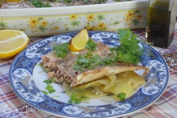 Достать блюдо из духовки, посыпать зеленью петрушки и подавать к столу, поливая рыбу соком печеного лимона.