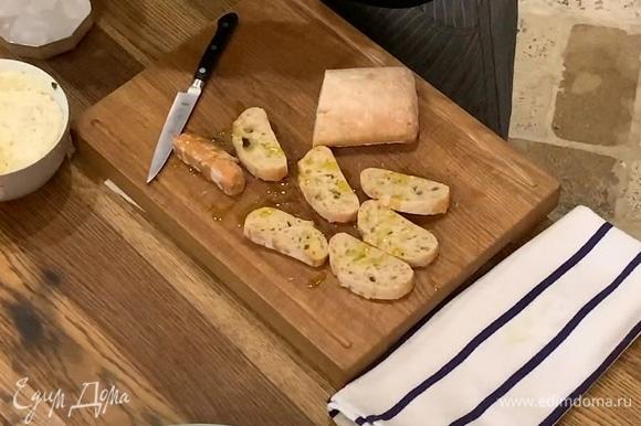 Хлеб нарезать ломтиками, сбрызнуть с двух сторон оставшимся оливковым маслом и обжарить на сухой сковороде-гриль.