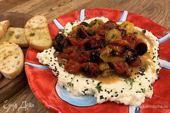 На большую тарелку выложить сырную смесь, посыпать оставшимся майораном, тимьяном и кунжутом, сверху разложить запеченные помидоры. Обжаренный хлеб подать на отдельной тарелке.