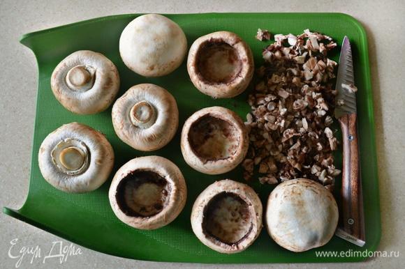 Шампиньоны (нам понадобятся достаточно крупные грибы) промойте, просушите и почистите. Острым ножом аккуратно вырежьте ножки и верхнюю часть шляпок. Вырезанные части грибов мелко порубите. Поместите очищенные шапки шампиньонов в форму для запекания, смазанную растительным маслом. Сверху немного сбрызните грибы маслом, накройте фольгой и запекайте в разогретой до 180°C духовке 20 мин.