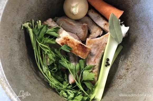 Мясо желательно брать на кости, нарезаем на средние куски, обжариваем в сковороде с растительным маслом до золотистой корочки. Выкладываем в емкость, где будем варить, добавляем веточки петрушки, морковь, мытую луковицу, сельдерей, лавровый лист, перец горошком. Заливаем 2,5 литрами воды, доводим до кипения, уменьшаем огонь и томим, пока мясо не начнет отходить от кости (1,5–2 часа).