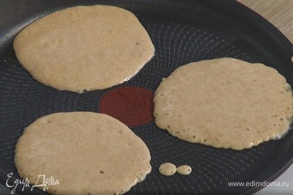 Разогреть блинную сковороду, кисточкой смазать ее растительным маслом и, наливая половником тесто, жарить блинчики по 2 минуты с каждой стороны.