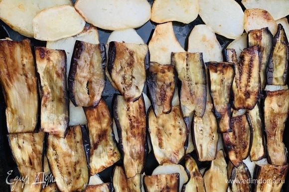Собираем мусаку. На противень послойно выкладываем обжаренные дольки картофеля. На них кладем баклажаны.