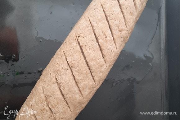 Получившийся рулет переложить на смазанный растительным маслом противень швом вниз, защипать края и аккуратно сложить их. На ровном красивом батоне делаем надрезы острым ножом, накрываем полотенцем и оставляем на 30–40 минут подходить.