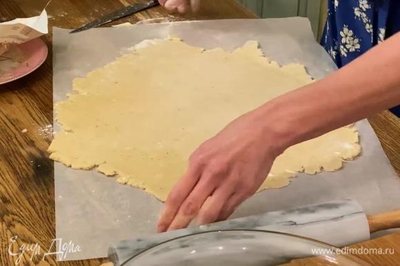 Выложить тесто на лист бумаги для выпечки и раскатать в тонкий корж.