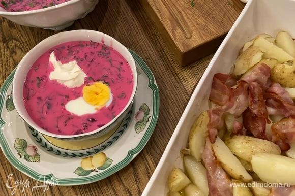 Разлить холодник в тарелки, добавить в каждую половинку яйца и столовую ложку сметаны. К супу подать картофель с беконом.