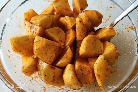 Картофель нарезать небольшими кусочками. Добавить соль, паприку, перец, розмарин и оливковое масло. Перемешать.